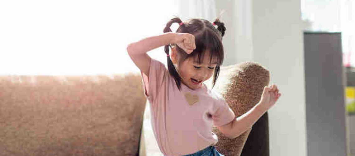 Little girl dancing in front of couch